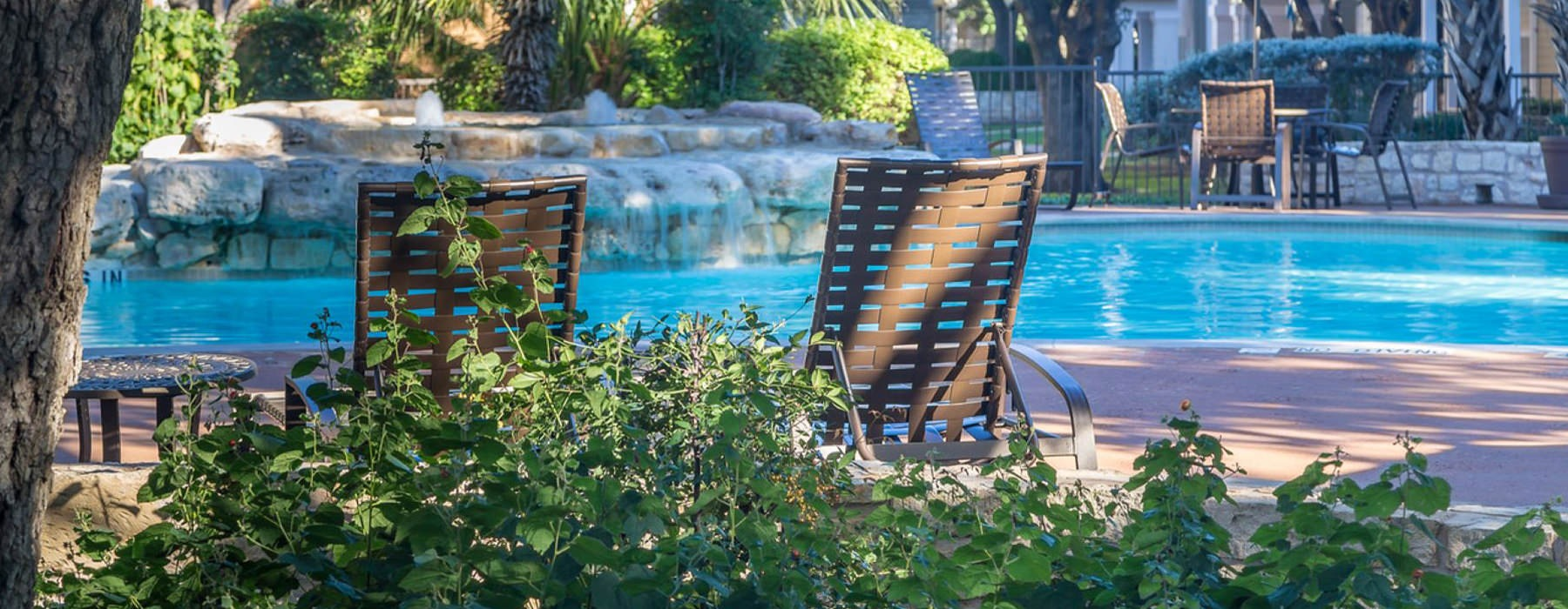 Lounge chairs by a pool with a fountain